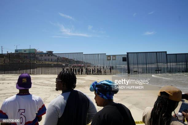 Worshipers in the US interact with people on the Mexico side of the border before a binational Easter mass along the USMexico border fence at...