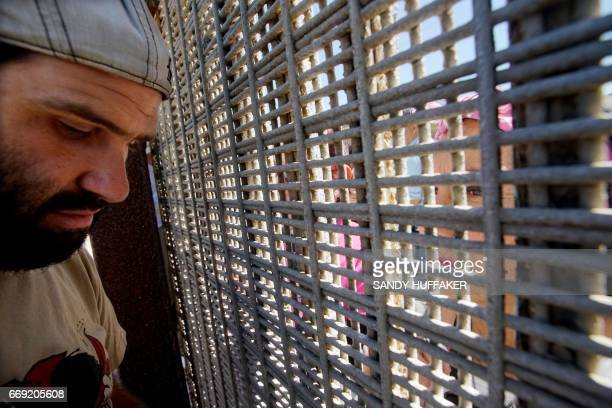 Worshipers interact with each other during in a binational Easter mass along the USMexico border fence at Friendship Park in San Ysidro California on...
