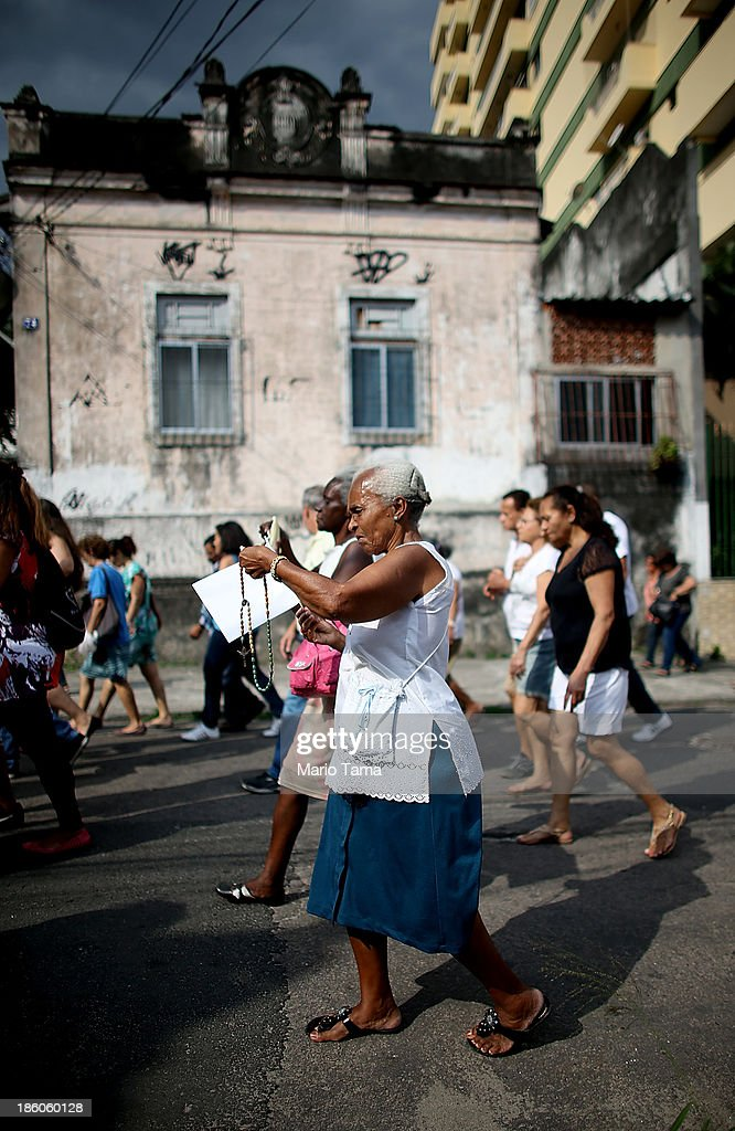 Worshipers march during a procession near the Nossa Senhora da Penha Church on the final day of the annual October feast of the patron saint marking the 378th anniversary of the church on October 27, 2013 in Rio de Janeiro, Brazil. Pilgrims often climb the entire 382 steps that lead to the church, originally constructed in 1635, which is perched on a rocky hill. Brazil holds more Catholics than any other country.