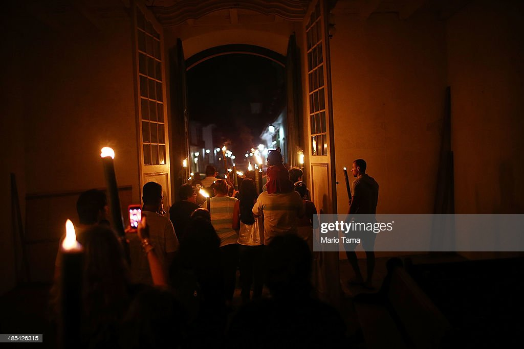 Worshipers march through a historic church while carrying bamboo torches during the traditional 'Procissao do Fogareu' (Procession of the Torches) through the historic center of town during Semana Santa (Holy Week) festivities on April 18, 2014 in Paraty, Brazil. Holy Week marks the last week of Lent and the beginning of Easter celebrations for Catholics. Brazil holds more Catholics than any other country. Paraty was built as a Portuguese colonial town shortly after Portugal colonized Brazil in 1500. Paraty flourished during the 18th Century as the main port to ship Brazilian gold to Portugal. The town center is well preserved and the cobblestone streets remain closed to automobiles.