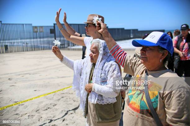 Worshipers wave to people on the Mexico side of the border before participating in a binational Easter mass along the USMexico border fence at...