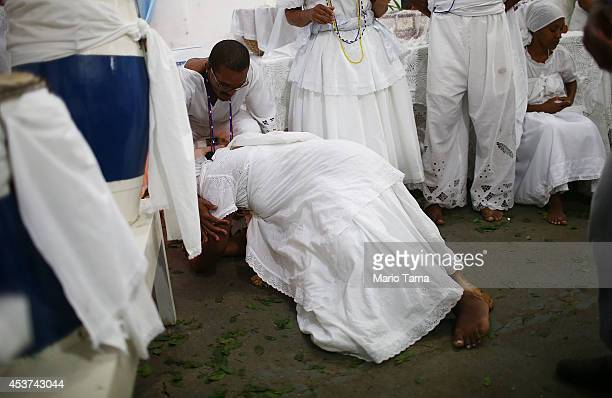 A worshipper bows after falling into a trance during a Candomble ceremony on August 17 2014 in Cachoeira Brazil Candomble is an AfroBrazilian...