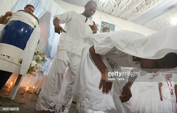 A worshipper dances after falling into a trance during a Candomble ceremony on August 17 2014 in Cachoeira Brazil Candomble is an AfroBrazilian...