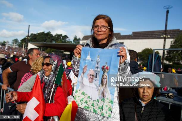 A worshipper holds a banner with images of Pope Francis and Our Lady of Fatima as she waits for the start of the ceremony of canonization at the...