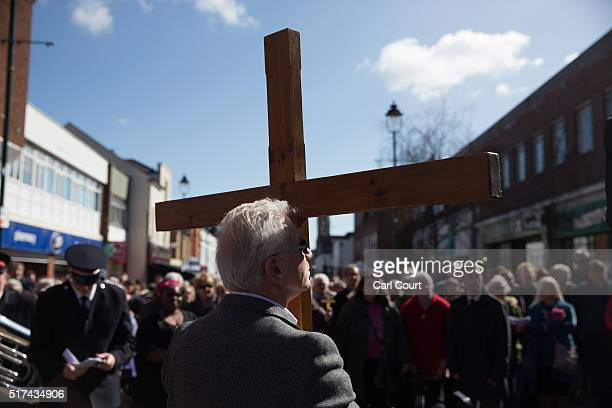 A worshipper holds a crucifix as a service is delivered after a March of Witness through the town centre on March 25 2016 in Sittingbourne England...
