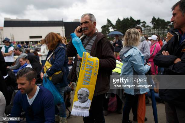 A worshipper holds a scarf with the image of Pope Francis at the Sanctuary of Fatima on May 12 2017 in Fatima Portugal Pope Francis will be attending...