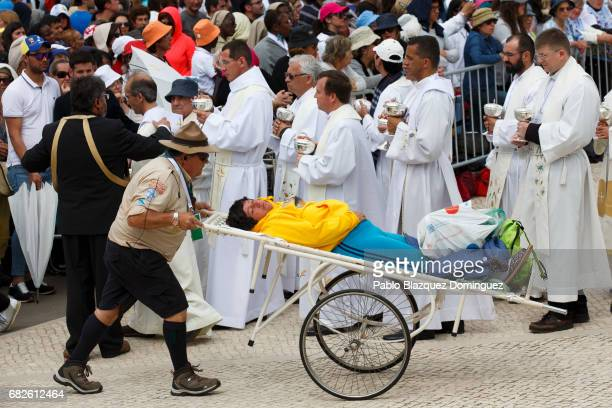 A worshipper is carried to receive medical help during the mass of canonization at the Sanctuary of Fatima on May 13 2017 in Fatima Portugal Pope...