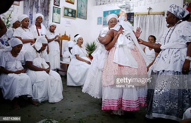 A worshipper is hugged dressed as the goddess Iansa after falling into a trance during a Candomble ceremony on August 17 2014 in Cachoeira Brazil...