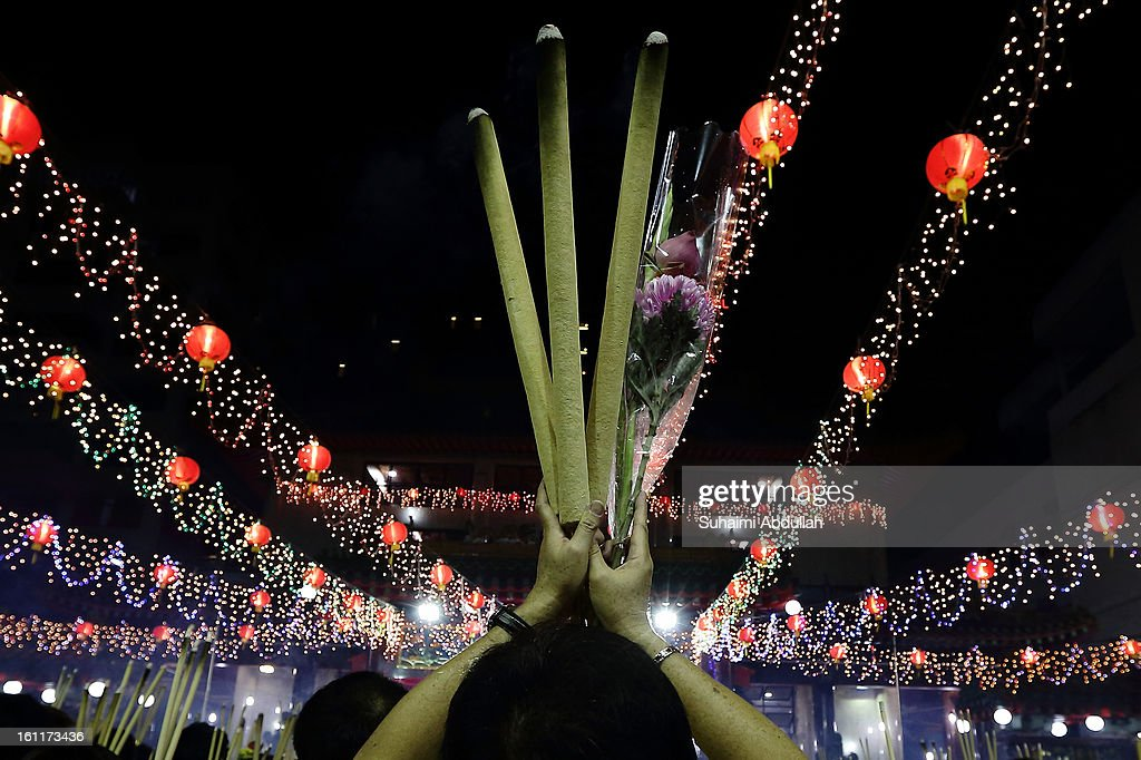 A worshipper is seen holding up the joss stick to pray at the Kwan Im Thong Hood Cho Temple on Lunar New Year on February 10, 2013 in Singapore. Thousands gathered today to celebrate the Chinese New Year and welcome the the Year of the Snake, with new year's day falling on February 10. Chinese new Year is the most important festival in the Chinese calendar and is celebrated in Singapore and many other Southeast Asian countries with significant Chinese Populations.