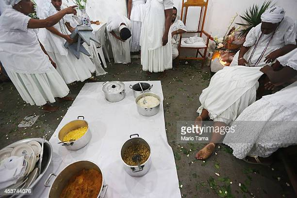 A worshipper kneels on the floor after falling into a trance as a meal is prepared during a Candomble ceremony on August 17 2014 in Cachoeira Brazil...