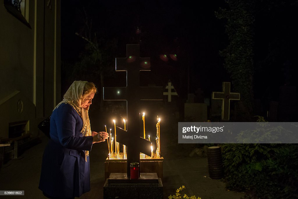 A worshipper lights candle during the Orthodox Easter ceremony in front of the Orthodox Church of the Dormition at the Olsany Cemetery on May 1, 2016 in Prague, Czech Republic. The Greek Orthodox world celebrates Easter Day according to the old Julian calendar.