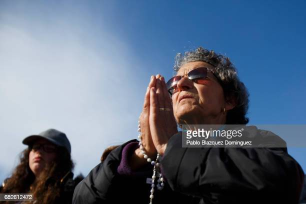 A worshipper prays before the start of the ceremony of canonization at the Sanctuary of Fatima on May 13 2017 in Fatima Portugal Pope Francis is...