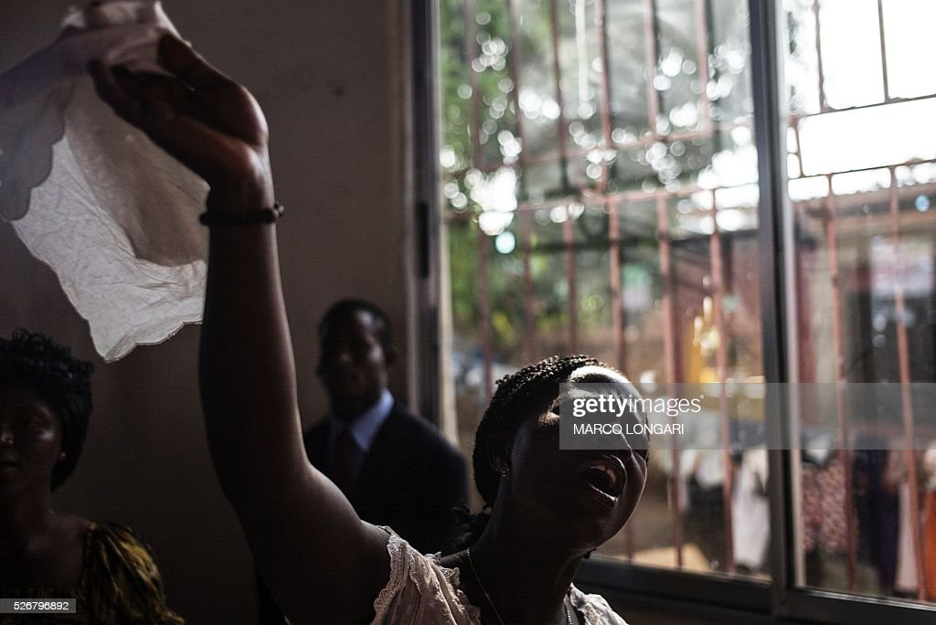 A worshipper prays during a service at the Winners Chapel International in the Weasay district of Monrovia on May 1, 2016. / AFP / MARCO
