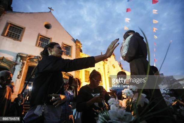 A worshipper reaches to touch the statue of Saint Anthony at the annual feast of Saint Anthony of Padua at the Santo Antonio convent on June 13 2017...