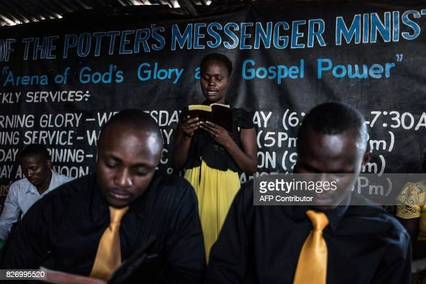 A worshipper reads a scripture during a service at the Voice of the Potter's Messenger Church on August 6 2017 located at the entrance to Obunga slum...