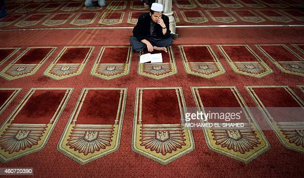 A worshipper reads from the Koran Islam's holy book inside AlAzhar mosque in the old city of Cairo on December 20 2014 AlAzhar mosque which was...