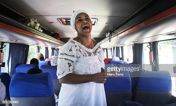 A worshipper sings while taking a bus to a beach on Guanabara Bay during a Candomble ceremony honoring goddesses Iemanja and Oxum on December 13 2015...