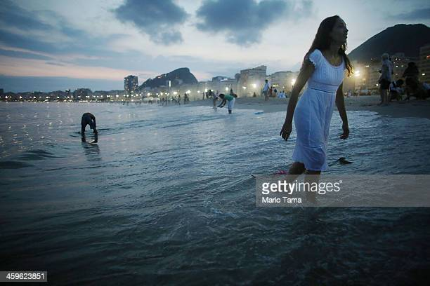 A worshipper walks away after tossing offerings into the ocean during a ceremony honoring Iemanja Goddess of the Sea as part of traditional New...