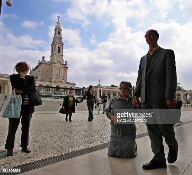 A worshipper walks on her knees as she prays for the Pope as her husband holds her hand while another woman prays as well at the Fatima Sanctuary in...