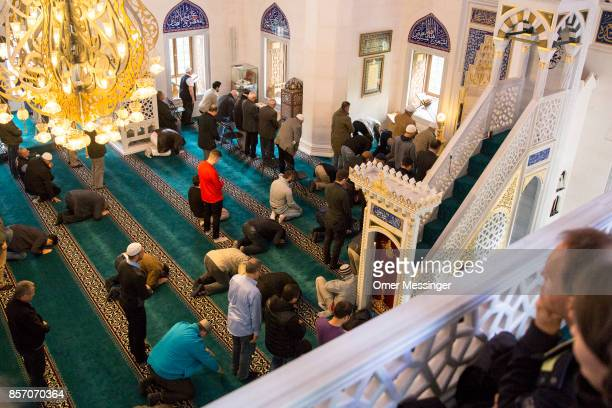Worshippers are seen during midday prayers as visitors watch them from above at Sehitlik mosque which is mostly Turkish on Open Mosque Day on October...