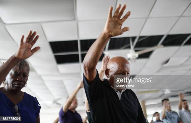 Worshippers attend Sunday mass in a church with roof and ceiling damage and without electricity on October 15 2017 in San Isidro Puerto Rico Puerto...