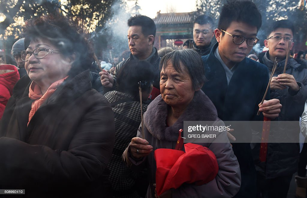 Worshippers burn incense and pray for good luck at the Yonghegong Lama Temple on the first day of the Lunar New Year in Beijing on February 8, 2016. Millions of Chinese began celebrating the 'Spring Festival', the most important holiday on the Chinese calendar, which this year marks the beginning of the Year of the Monkey. AFP PHOTO / GREG BAKER / AFP / GREG BAKER