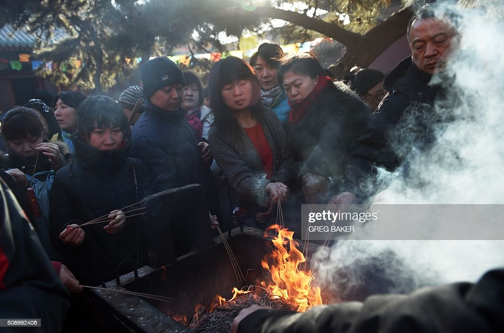 Worshippers burn incense for good luck at the Yonghegong Lama Temple on the first day of the Lunar New Year in Beijing on February 8, 2016. Millions of Chinese began celebrating the 'Spring Festival', the most important holiday on the Chinese calendar, which this year marks the beginning of the Year of the Monkey. AFP PHOTO / GREG BAKER / AFP / GREG BAKER