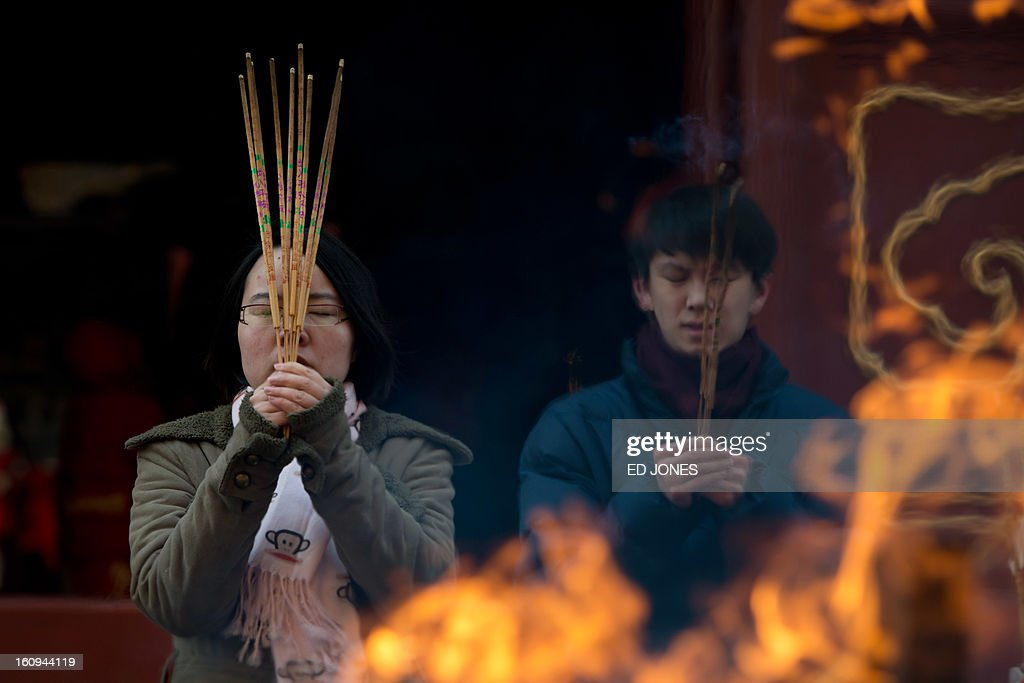 Worshippers burn incense while offering prayers at the Yonghegong lama temple in Beijing on February 8, 2013. China is preparing to welcome the lunar new year, or spring festival, which falls on February 10. AFP PHOTO / Ed Jones