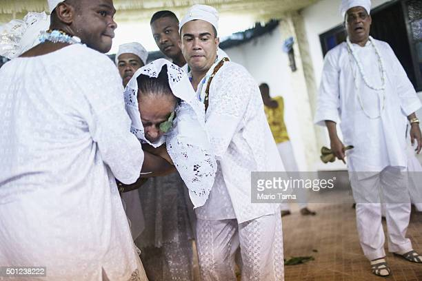 Worshippers carry another who they said became possessed by a spirit during a Candomble ceremony honoring goddesses Iemanja and Oxum on December 12...