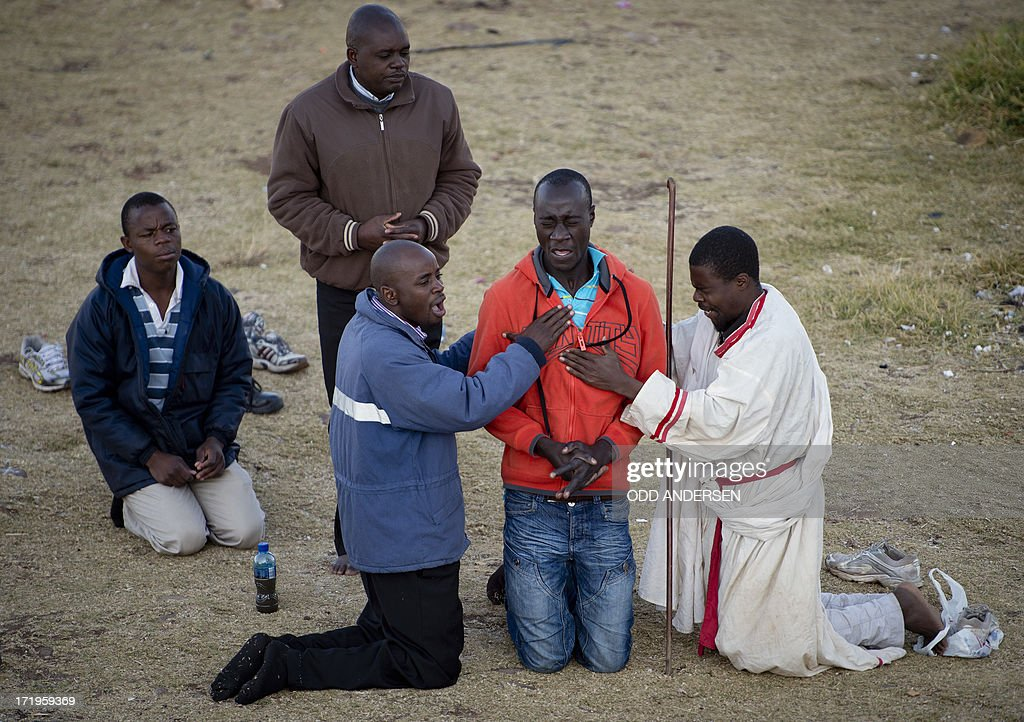 Worshippers from a Baptist church perform exorcism on a congregation member in the Hillbrow neighbourhood overlooking down town Johannesburg on June...