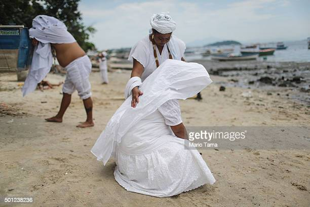 Worshippers gather along the beach on Guanabara Bay during a Candomble ceremony honoring goddesses Iemanja and Oxum on December 13 2015 in Sao...