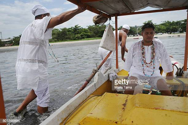 Worshippers gather on a boat on polluted Guanabara Bay during a Candomble ceremony honoring goddesses Iemanja and Oxum on December 13 2015 in Sao...