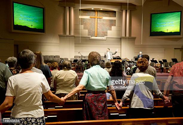 Worshippers join hands during a church service July 22 2012 in Aurora Colorado Many residents affected by the attack at a midnight premiere of...