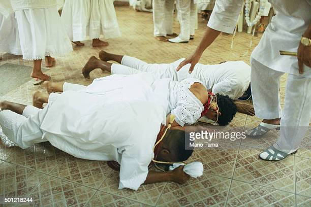 Worshippers lie on the floor during a Candomble ceremony honoring goddesses Iemanja and Oxum on December 12 2015 in Itaborai Brazil Candomble is an...