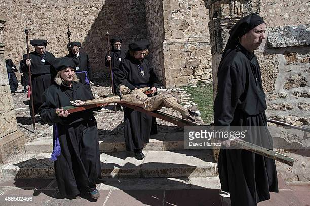 Worshippers of the brotherhood of 'La Cofadria de la Vera Cruz y El Cristo de las Lluvias' walk the way of the cross or 'Via Crucis' in Alustante on...