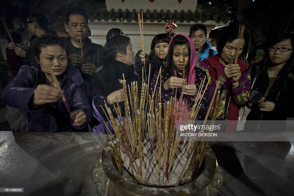 Worshippers place incense sticks as they pray to welcome in Chinese Lunar New Year at the Wong Tai Sin Temple in Hong Kong on February 10, 2013. Chinese lunar new year, celebrated by Chinese communities the world over, falls on February 10 with the beginning of the new moon. AFP PHOTO / Antony DICKSON