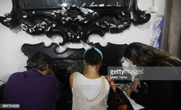 Worshippers pray and write messages beneath a painting of Saint Anthony at the annual feast of Saint Anthony of Padua at the Santo Antonio convent on...