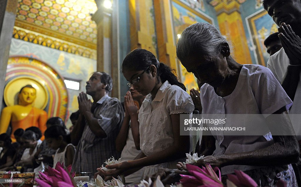 Worshippers pray at a temple in Colombo on January 1, 2013 to welcome in the New Year. Asian cities brought in the New Year in spectacular style the night before after Sydney set off a global wave of fireworks, with long-isolated Yangon joining the pyrotechnic celebrations for the first time.