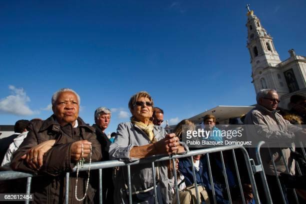 Worshippers pray before the start of the ceremony of canonization at the Sanctuary of Fatima on May 13 2017 in Fatima Portugal Pope Francis is...