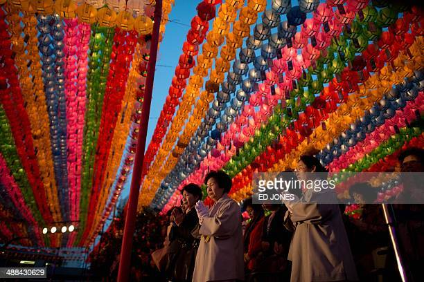 Worshippers pray beneath lanterns during a ceremony marking Buddha's birthday at the Jogyesa temple in Seoul on May 6 2014 Buddha's birthday in South...