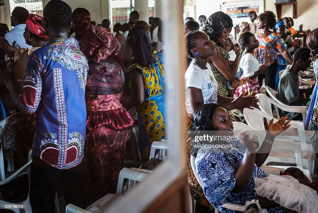 Worshippers pray during a service at the Winners Chapel International in the Weasay district of Monrovia on May 1, 2016. / AFP / MARCO