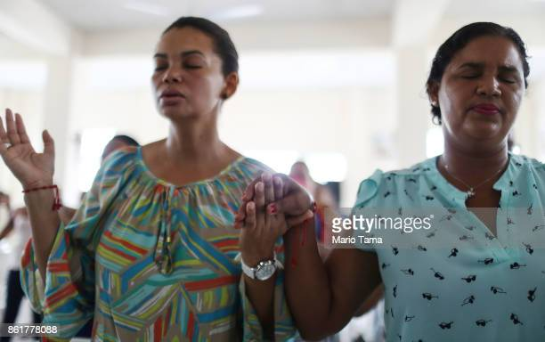 Worshippers pray during Sunday mass in a church without electricity on October 15 2017 in San Isidro Puerto Rico Puerto Rico is suffering shortages...