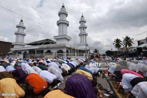 Worshippers pray in front of the Koumassi Mosque for the Eid alFitr holiday on June 25 2017 in Abidjan Muslims worldwide celebrate the Eid alFitr...