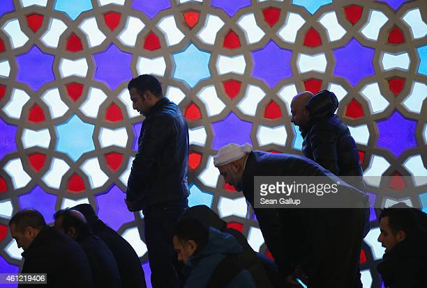 Worshippers standing in front fo a stainedglass window attend midday Friday prayers at the Turkishspeaking Sehitlik Mosque on January 9 2015 in...
