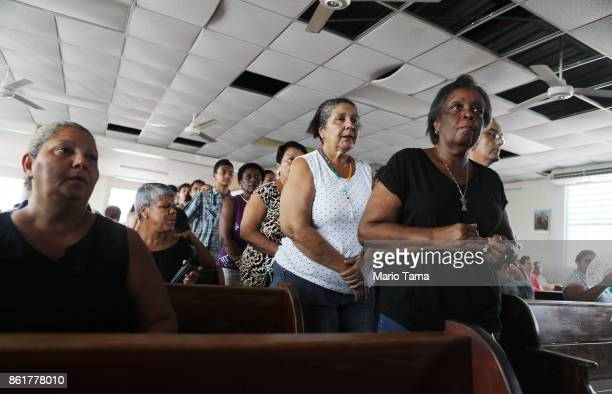 Worshippers wait to take communion during Sunday mass in a church with roof and ceiling damage and without electricity on October 15 2017 in San...