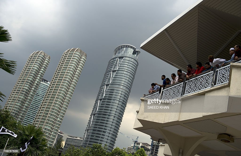 Worshippers watch residential high-rise projects from the second floor of a mosque after a mass Friday prayer in the business hub of Kuala Lumpur on January 11, 2013. Malaysia's economy grew a better-than-expected 5.2 percent in the third quarter as domestic demand compensated for the weakening exports, spurred on by government spending ahead of elections this year. The government has forecast 5.0 percent full-year growth for 2012. AFP PHOTO / Saeed Khan