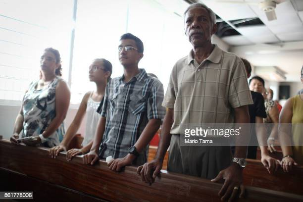 Worsippers attend Sunday mass in a hurricanedamaged church without electricity on October 15 2017 in San Isidro Puerto Rico Puerto Rico is suffering...