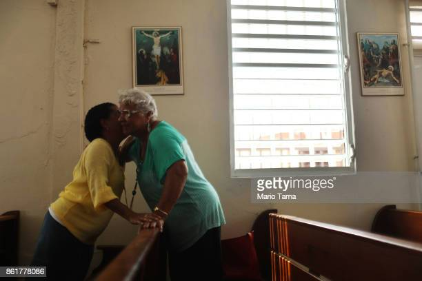 Worsippers hug following Sunday mass in a hurricanedamaged church without electricity on October 15 2017 in San Isidro Puerto Rico Puerto Rico is...
