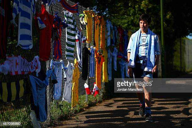 Worthing United fan walks past football shirts attached to a fence in memory of Matthew Grimstone and Jacob Schilt two Worthing United players who...