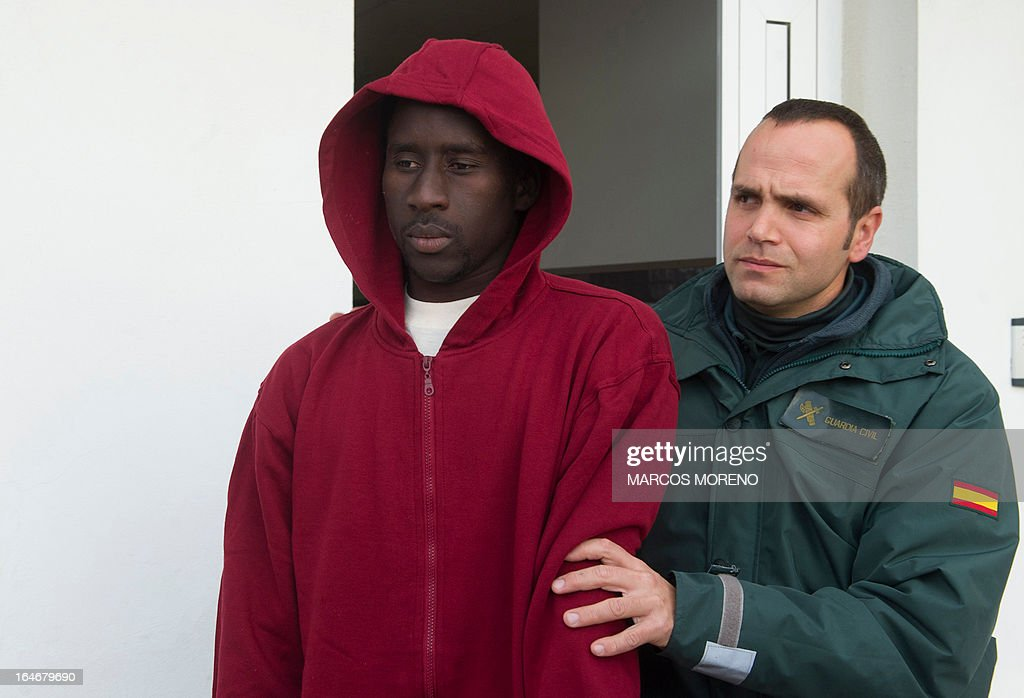 A would-be immigrant is escorted by a Guard Civil policeman as he arrives at a shelter of Spanish emergency services in Tarifa after being rescued off the Spanish coast, on March 26, 2013. Spanish emergency services rescued two inflatable boats carrying five and seven sub-Saharan would-be immigrants across the Strait of Gibraltar. A third one was rescued by Morrocan authorities.